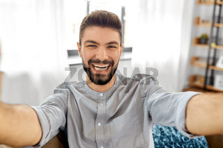 man taking selfie or having video call at home