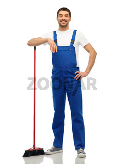 male cleaner in overall cleaning floor with broom