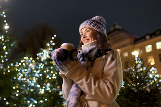 happy woman drinking coffee over christmas lights