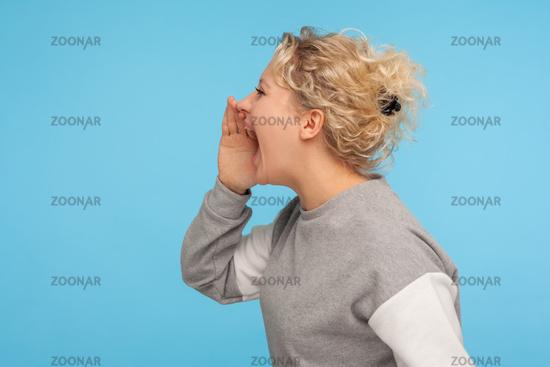 Portrait of emotional blonde woman on blue background.