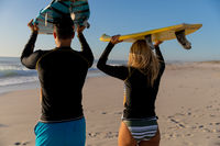 Caucasian couple holding surfboards at the beach.