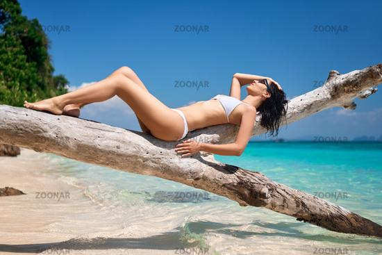 Pretty slim woman in white bikini sunbathe and relax on tropical beach.