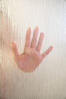 female hand behind frosted glass shower screen
