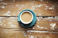 Photo of hot coffee with milk in blue porcelain cup