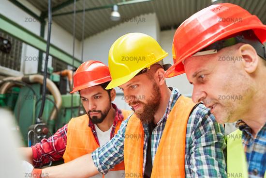 Gruppe Metallarbeiter bei der Planung in Teamwork