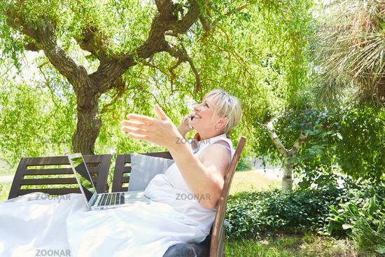 Senior Frau führt ein Telefonat im Sommer im Garten