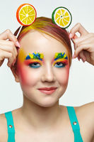 Teenager girl with unusual face art make-up . Child with lollipops in hands on head like ears.