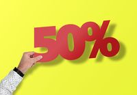 hand holding red 50 percent sign against yellow background