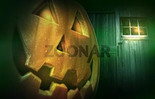 Glowing pumpkin at night in front of barn door