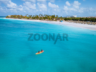 Couple Kayaking in the Ocean on Vacation Aruba Caribbean sea, man and woman mid age kayak in ocean blue clrea water