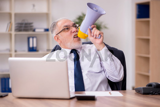 Old male employee holding megaphone at workplace