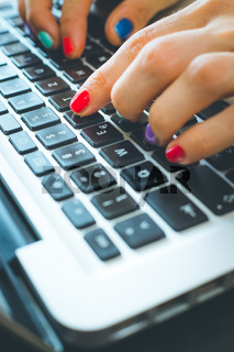 Home office or online shopping: Woman fingers with colorful nails are typing on a notebook keyboard