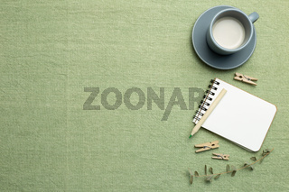 Notebook, cup of milk, pencil with eucalyptus on green fabric background. flat lay, top view, copy space. Work and study place