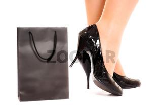 women legs in fashion shoes near shopping bag