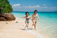 wo young women friends having fun and running on the tropical beach during summer vacation
