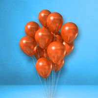 Orange balloons bunch on a blue wall background