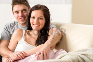 Carefree young couple embracing on couch