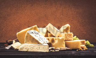 Different types of cheese on black wooden table background