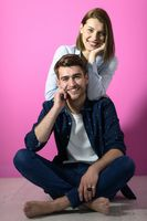 couple sitting on the floor while posing in front of a pink background