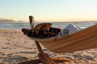 Mixed race woman on beach holiday lying in hammock