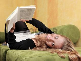 Frau auf dem Sofa beim lesen eines Buches