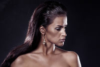 Fashion brunette. Portrait of beautiful woman wearing earrings.