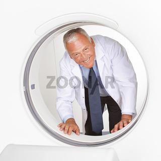 Arzt schaut durch Röhre im MRT