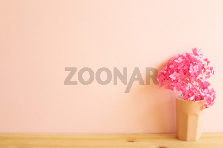 Vase of dry pink hydrangea flowers on wooden table. Pink background, copy space