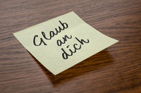Sticky note with the text Believe in you in german - Glaub an dich