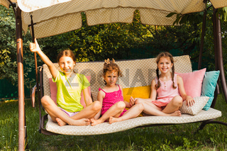 Three lovely sisters on soft garden swing