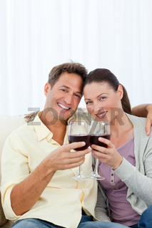 Lovely couple drinking red wine on the sofa