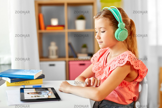 girl with tablet pc having online class at home