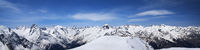 Panorama of high snow-capped mountain peaks and beautiful blue sky with clouds at sunny day