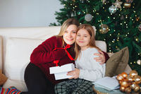 Joyful grandmother and lovely girl granddaughter in cozy knitted sweaters by Christmasmas fir tree in living room