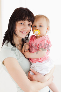 Good looking woman holding her baby in her arms while standing