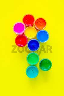 A creative flower made up of jars of paint on a yellow background