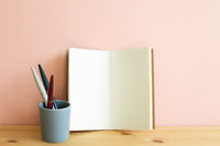 Open blank notebook and pen on wooden desk. Pink background, copy space. Work and study place