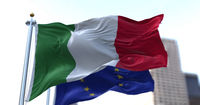 The national flag of Italy waving in the wind together with the European Union flag blurred in the background