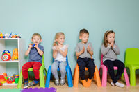 Children are sitting on the colorful chairs in the kindergarten