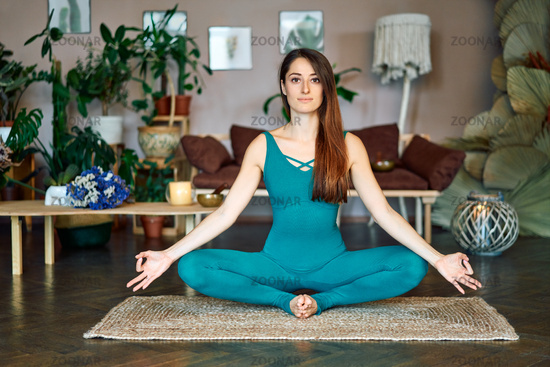 Young woman practicing yoga doing Butterfly Pose with mudra hands at home