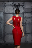 Young woman in black rabbit or hare fancy mask and red dress from back side. I