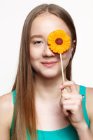 Teenager girl with flower lollipop in hands closing eye.