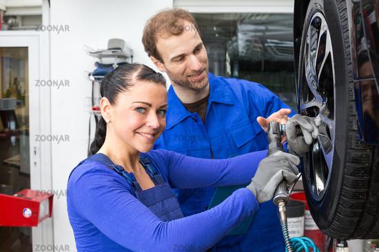 Kfz Mechaniker beim Wechsel eines Reifens