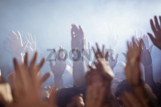 Crowd with arms raised enjoying at nightclub