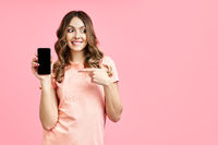 Excited woman pointing her finger at mobile phone and looking to copy space