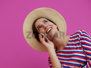 Portrait of young girl with happy face while using smartphone isolated on pink background