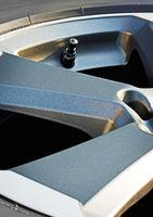 Detailaufnahme von modernen Autoreifen mit Alufelge und Wassertropfen, Hochformat
