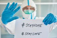 Klinik Personal mit #stayhome ä#staysafe Schild