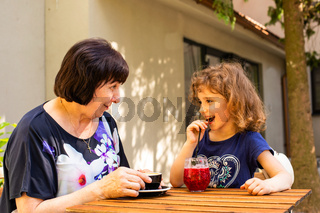 Little girl and her grandmother drink coffee and cocktail