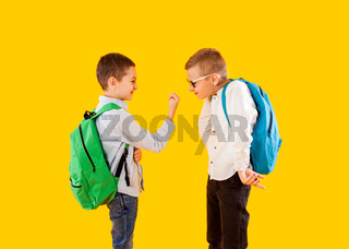 Cute schoolboys in uniform with backpacks on yellow background